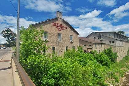 The historic limestone two-storey building of the Brew House Pub & Grill overlooks the Grand River as it winds through downtown Fergus. Here there are many trees and bushes along the rocky shoreline leading up to the wall. Four windows overlook the river, while above three windows offer a view to B & B guests. The restaurant on the lower level includes a patio at the back of the building, connecting it to a series of other heritage stone buildings with modern roofs and additions.