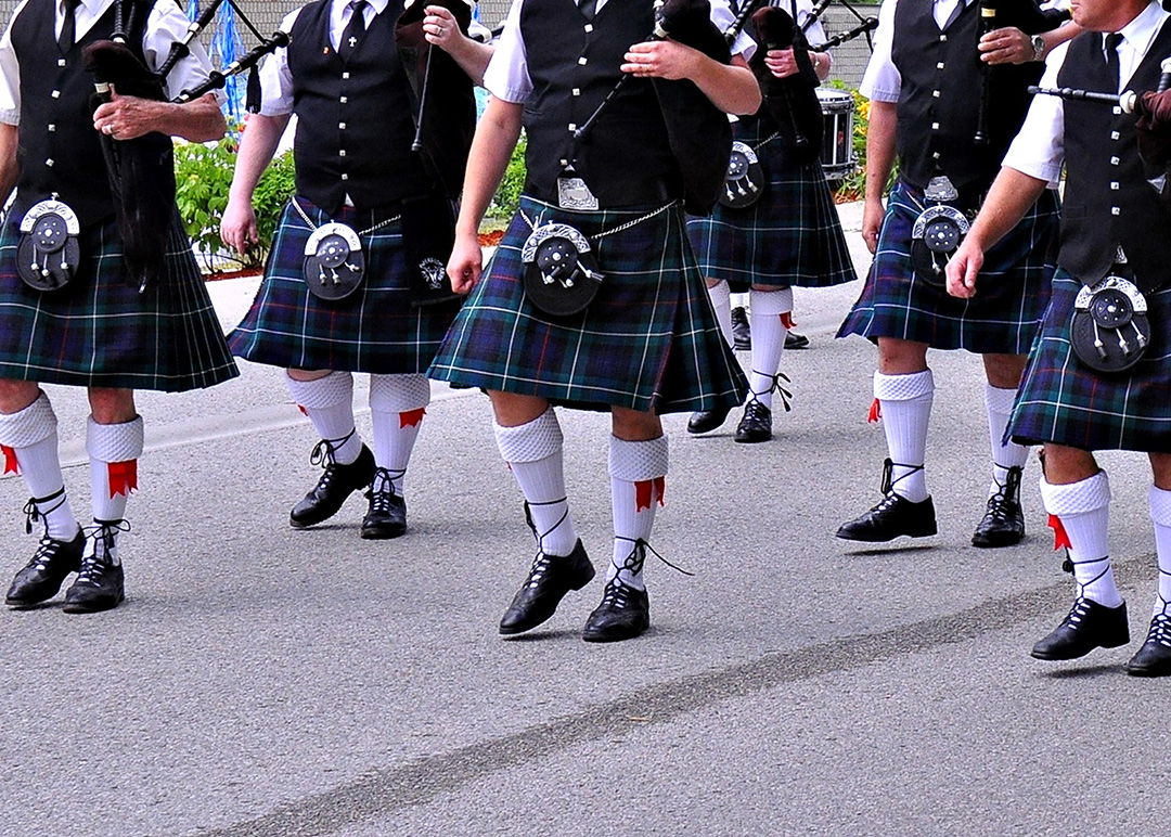 A tartaned clad bagpipe band marches along a road. The image doesn't show the heads of the all-male participants. It shows the bagpipers from the shoulders down, wearing black vests with silver square buttons. The tartan plan kilts are dark blue with green, purple and white patterns. Each piper wears a silver and black leather sporan, white knit socks up to the knee with red sashes and black leather lace-up kilt shoes. This photo is of members of the Fergus Pipe Band.