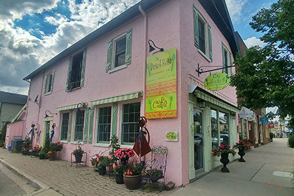 A picturesque pink stucco exterior with green trim makes the two-storey Desert Rose Cafe building a landmark corner site in downtown Elora. The large bright green and orange sign mid-wall on the south side of the building displays the Desert Rose Cafe name. Flowers and ornamental garden art adorn the south side of the building, beneath the green framed windows. The East facing side or front of the restaurant faces Geddes Street and the main sidewalk. The front store windows and door are framed in green. Out front a small bright green sign displays the business name hung from a wrought iron pole.