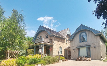 Heritage stone home with sculpted trestle roof and garden.