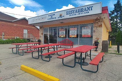 An exterior image of a building with stone exterior in the front, with four large window panels and a glass door at the far left to enter the establishment. Out front are 3 red picnic tables bordering the parking lot. A red bench backs up against the windows. Along the extension of the roof is a sign that reads Golden Fish & Chips Restaurant.