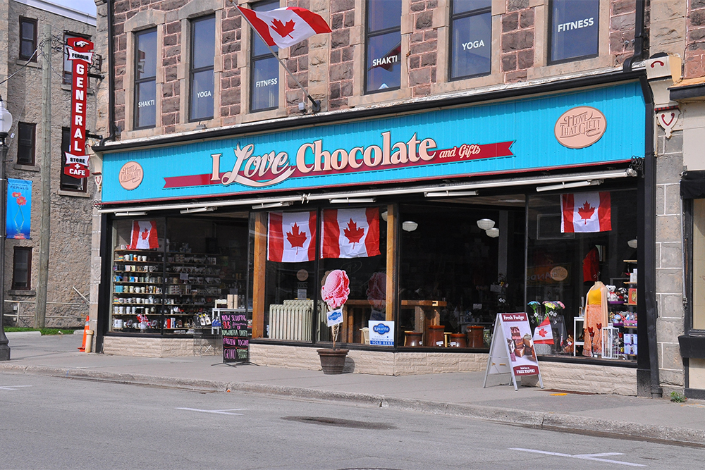 An outside image of the storefront for I Love Chocolate in downtown Fergus. The store is located on the street level of a stone block heritage building. The storefront is all windows that are flat with the building and then turn into it to create two separate alcoves, with two doors that are in the alcoves. Across the length of the store, above the windows, is a bright blue wooden panelled wood sign that bears the store logo: I Love Chocolate and Gifts. On each end of those words is a an oval sign in light brown. On the left of the sign it reads: I love that chocolate. On the right of the main sign, the oval sign reads: I love that gift. The windows offer a full view of the interior of the store. There are two sandwich boards outside each end of the building displaying their fudge and daily specials.