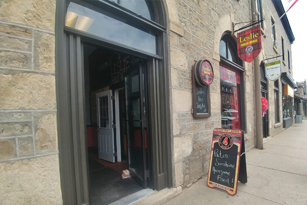 Exterior stone walls of a heritage building in downtown Fergus with a rounded windows atop a large, dark painted wooden doorframe, where the door is open to an interior alcove, where a white door on the right side leads into the pub. The stone building is part of a larger unit, and has a rounded window atop a square framed window, beneath a flag sign in a red and black tartan print that reads Leslie Public House in yellow letters. A round wooden sign is attached to the front of the building that has the same tartan and logo on it, with a chalkboard attached. A sandwich board on the sidewalk out front displays the daily features.