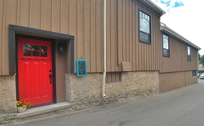Exterior of a brown siding building with stone foundation and a large, bright red door with black trim. A flower pot sits outside the door entrance. A small blue framed chalkboard details the daily specials.