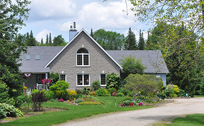 A modern, two-storey grey brick country home with gardens and a gravel driveway.