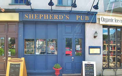 "Exterior heritage building with deep blue wood panelling and three windows set midway, each displaying a local event poster. Double blue framed doors are on the step up on the far right side of the pub. Large blue metal lights curve to hang over the gold lettered sign that reads"" Shepherd's Pub. A red potted plant is left of the doors, to the right is a blue framed menu board. A sandwich board sign to the right of the signs lists the daily specials and what's on tap."