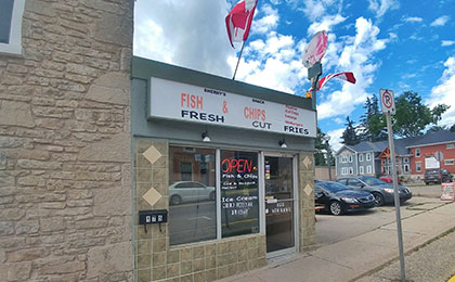 Exterior of a small brick building with double large window panes and a glass door. Above the window and doors is green siding with a large white sign that reads: Fish and Chips, Fresh Cut Fries. Three Canadian flags are attached to the top of the sign. A pedestrian sidewalk is out front of the store.