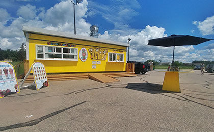 A small bright yellow chip wagon building with two large order windows on each end of the front of the building, with the Fry Shack's cartoon French fry logo between them. Stairs and an accessibility ramp lead up to the building.