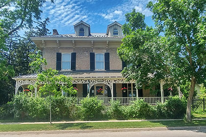 A historic home with a fully renovated carriage house has become the Drew House Bed & Breakfast in Elora. The main house, a Victorian-style stone house with two-storeys and an attic with dormers features a wrap around porch with ornate details along the roof and railings in a light paint colour. The grand home has three windows on the second storey with black shutters. Under the patio is a front door, centered between two windows, all with long black shutters. The veranda has hanging baskets of flowers and a garden of bushes and trees that obscure the foundation of the house.
