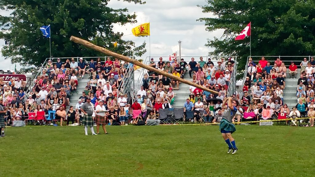 Fergus Scottish Festival and Highland Games caber toss event with an athlete throwing the caber in mid-air before a crowd of onlookers on the bleachers.