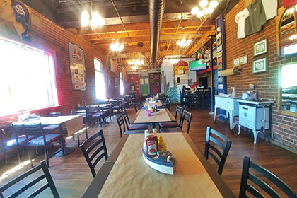 An interior image of the Goofie Newfie restaurant in downtown Fergus, with a Newfoundland decor and atmosphere. The room has high beam ceilings and hardwood floors with large windows on the left side and an interior brick wall on the right side. Furnished with antiques, the wooden tables have Dory boat centre pieces that hold the condiments, with wooden chairs for seating.