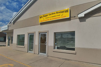 A modern building with two-tone beige exterior and two large windows, with two glass doors in between them. One door is the main entrance to the building. Above it is a yellow sign displaying New Happy Garden Restaurant, Canadian and Chinese Food, Dine-In & Take-Out