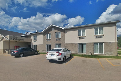 The Village Inn Elora is a two-storey grey brick building with rooms on each level. Street level rooms has sliding glass doors. The second storey rooms have large windows. All rooms overlook the parking area.