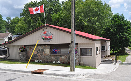 Restaurant building in Belwood with stone front wall and beige siding, with a red roof.