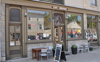 Store front for Cafe Creperie with two large windows and a window-panelled door into a limestone building, with cafe tables and chairs and a sandwich board out front.
