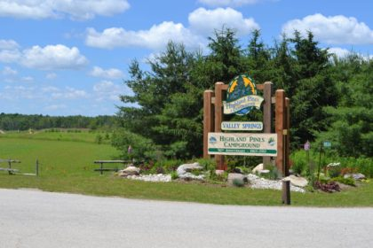 The main entrance signage for the Highland Pines Campground - Valley Springs - Highland Pines Campground, 50th Anniversary 1967-2017. The wooden painted sign on several large timber posts sits in a rock and flower garden.