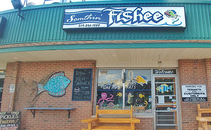 Exterior brick plaza storefront, with a window and door decorated in colourful cartoon fish and ocean creature paintings. Outside the store, a large blue fish plague rests on the wall next to a black chalkboard with the daily specials, and two wooden seating benches adorn each side of the front glass door.