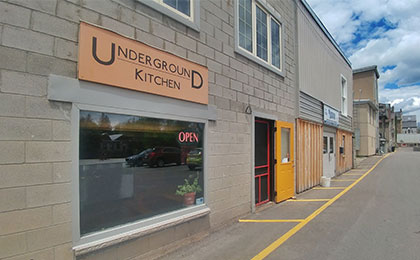 Exterior concrete block building, lower level, with a large window frontage beneath a sign that reads, Underground Kitchen, with a red screen-door entrance.