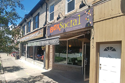 The exterior of the diner is next door to the Elora Brewing Company, to the left, and is part of the larger two-store limestone building. The store front has two large windows that are angled into building leading to a glass door on the right that is open. The storefront is shaded by a large awning that displays the address and phone number. Above that is a painted sign that extends the length of the storefront and reads: Box Social (in bright orange and green) Culture, Community, Food (in white). Three large black curved exterior lights bend over to light up the sign.