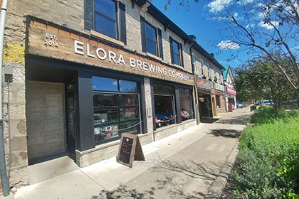 """A front view of the exterior heritage building, part of a larger section of buildings, that houses the Elora Brewing Company in a two-storey unit. The front of the brewery has three large windows that open fully in summer months. They are framed in black metal with a stone foundation. The main door to the retail and restaurant location is in an alcove on the far left of the windows. It opens into the side of the unit. Across the top of the black framed windows is a wooden backdrop sign that has large white letters that read"""" Est. 2014 Elora Brewing Company. Over the sign, three windows in black shuttered frames give light to the second story of the restaurant."""