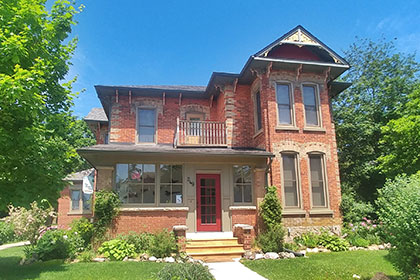 The Flying Leap Bed & Breakfast is a large two-storey Victorian home on a corner lot in downtown Elora. A heritage red brick home with ornate brick patterns, the house features many windows and a small balcony on the second floor. It has a large front closed-in porch accessible by four steps that lead to a large red front door. There are gardens trimmed with stone and a green lawn out with a concrete path leading guests into the house.
