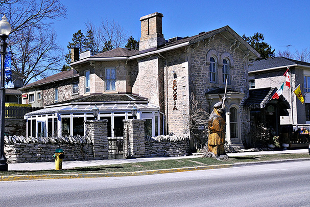 The historic stone home property known as the Breadalbane Inn in downtown Fergus is home to two restaurants, Scozia and the Fergusson Room pub. The exterior of the two-storey building is stone with a large rock-wall fence around an outdoor patio along the west side of the property, closed in with wrought iron gates. A large solarium overlooks the patio. Out front of the Breadalbane Inn is a large wooden stage of a man in a kilt holding up a sword, carved from a former tree on the property.