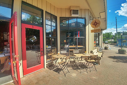 An outdoor image a cafe with a light green board and batten siding exterior, two large windows and a red framed windowed door that leads into the Lost and Found Cafe. Out front of the windows are a few wooden table and chair sets on the interlocking stone courtyard connecting the Elora Mews shops.