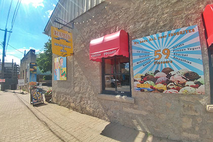 A limestone building on the corner of the Elora Mews features to walk-up windows for orders each with a red awning that display signs for frozen yogurt and ice cream. A large sign between the windows displays a photo of ice cream cones and the 59 flavours in a variety of frozen treat options.