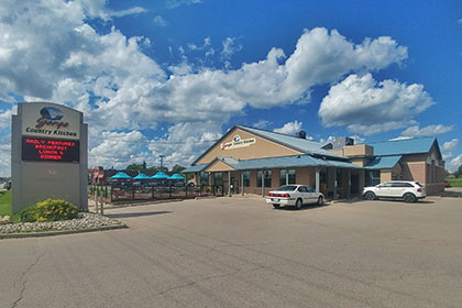 A large family restaurant, the brick building has several blue roofs, including a porch across the front and right side of the building with many windows around the building. On the roof top is a sign with the business name Gorge Country Kitchen. Our front of the building on the far left is a large outdoor patio with black iron fencing and tables adorned with bright blue umbrellas. At the edge of the parking lot, road side, is a large vertical digital sign with the Gorge Country Kitchen logo on top and a digital display screen beneath it.