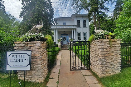 A street view of White Garden Bed & Breakfast shows a white brick heritage home with a large veranda with an entranceway into the home. The property has an elaborate wrought iron fence with wrought iron gates at the end of a stone pathway. The gates are connected to two stone pillars with some greener and a statue of a large peacock on each.